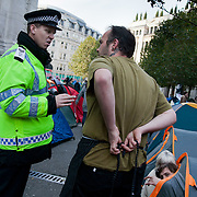 A police officer discussing with the chef from the make-shift kitchen whilst people are slowly waking up. Day three of the occupation - and the first Monday. The Occupy London Stock Exchange movement was formed in London in solidarity with the US based Occupy Wall Street. The movements are a respons and in anger to what is seen by many as corporate greed and a failed banking system being bailed out by the public, - which in return are suffering austerity measures to make up for the billions of lost money. The movement occupied the St Paul's Square in the City of London Sat Oct 15 after it failed to secure and occupy Pator Noster Square and the Stock Exchnage itself.
