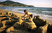 Boy building sandcastle on beach: Lido di Capoliveri.Island of Elba, Tuscany, Italy