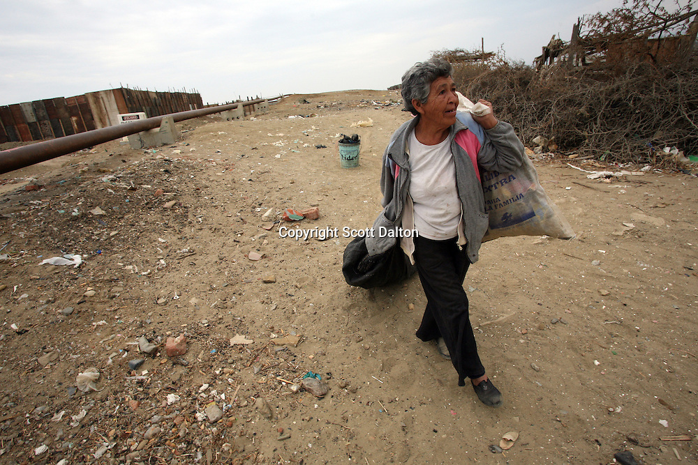 An elderly woman carries bags of recycled garbage near an oil pipeline on the outskirts of Talara, on Peru's northern coast on November 10, 2007. Talara is one of Peru's main oil producing regions and the Chinese company SAPET has an oil field in the region. (Photo/Scott Dalton)