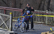 WASHINGTON (Jan 4, 2017) -- A U.S Park Police Officer escorts a bicyclist from the towpath area where a suspiciously stashed violin case was found containing two firearms, near Fletcher's Cove Boathouse on the C&O Canal late Wednesday morning Jan. 4, 2017.  More guns and ammunition were also found around the area.  Photo by Johnny Bivera