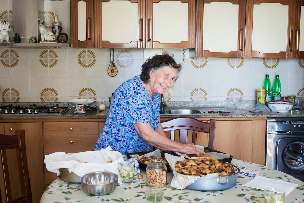 ACCIAROLI (POLLICA), ITALY - 5 OCTOBER 2016: 82-years old Fenisia La Greca prepares sun-dried figs stuffed with lemon zest, almonds and cinnamon, here in her kitchen in Acciaroli, a hamlet in the municipality of Pollica, Italy, on October 5th 2016. Fenisia La Greca grows fruit and vegetables in her own garden.<br /> <br /> To understand how people can live longer throughout the world, researchers at University of California, San Diego School of Medicine have teamed up with colleagues at University of Rome La Sapienza to study a group of 300 citizens, all over 100 years old, living in Acciaroli (Pollica), a remote Italian village nestled between the ocean and mountains in Cilento, southern Italy.<br /> <br /> About 1-in-60 of the area&rsquo;s inhabitants are older than 90, according to the researchers. Such a concentration rivals that of other so-called blue zones, like Sardinia and Okinawa, which have unusually large percentages of very old people. In the 2010 census, about 1-in-163 Americans were 90 or older.