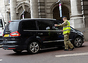 © Licensed to London News Pictures. 18/07/2012. Westminster, UK A soldier guides a car at Admiralty Arch Soldiers, police and security contractors perform security checks around Olympic sites in Westminster today, 18th July 2012. Photo credit : Stephen Simpson/LNP