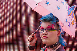London, June 28th 2014. A transexual participant uses a tiny umbrella as the Pride London parade proceeds through the city's streets.