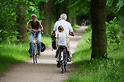 In de omgeving van Soest genieten mensen op de fiets van het mooie weer tijdens het Pinksterweekeinde. Een meisje zit achterop de fiets.<br />