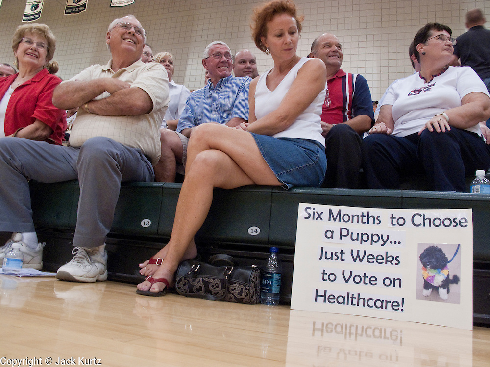 """Aug 10, 2009 -- CHANDLER, AZ: CECE WEST, from Queen Creek, AZ, sits next to a sign she brought to a town hall meeting on health care reform in Chandler, AZ. Rep. Jeff Flake, (R-AZ) hosted a """"town hall"""" style meeting on health care reform at Basha High School in Chandler Monday. Flake, a conservative Republican, has opposed President Obama on many issues, like the stimulus and health care reform. Protestors who have shut down similar meetings hosted by Democrats, gave Flake a warm welome. About 1,600 people attended the meeting.   Photo by Jack Kurtz"""