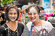 14 APRIL 2013 - BANGKOK, THAILAND:  Women with talc on their face walk through a water fight on April 14, 2013 in Bangkok, Thailand. The Songkran festival is celebrated in Thailand as the traditional New Year's Day from 13 to 15 April. The throwing of water originated as a way to pay respect to people and is meant as a symbol of washing all of the bad away. PHOTO BY JACK KURTZ