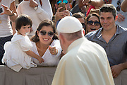 Pope Francis greets a mother and child at the General Audience.