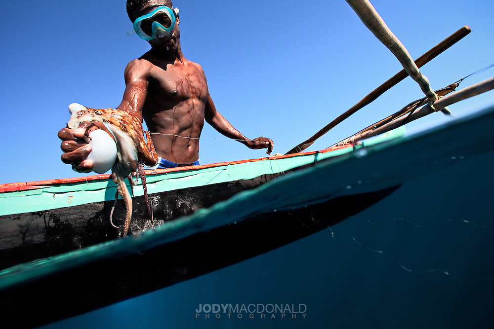 Vezo fisherman captures an Octopus near Anakao, Madagascar. Using the rudimentary fishing impliments these men make a living of capturing octopus to sell to the local village.