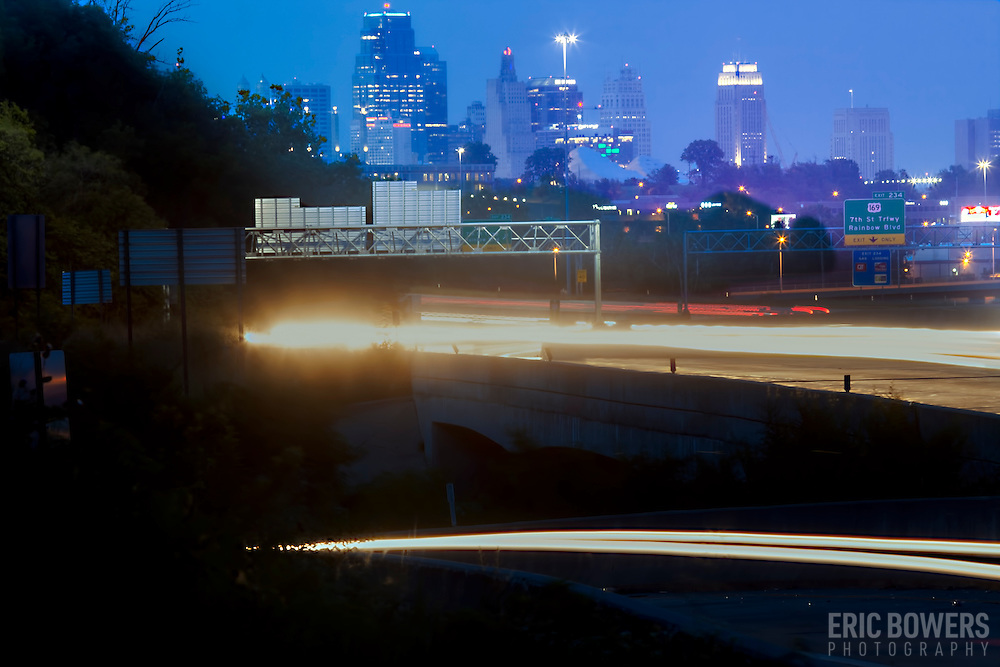 Telephoto view of Kansas City Missouri skyline, with highway car traffic motion blur on Interstate 35 in the foreground; taken from side of I-35 near Mission Road in Kansas.
