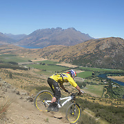 Brook MacDonald in action during the New Zealand South Island Downhill Cup Mountain Bike series held on The Remarkables face with a stunning backdrop of the Wakatipu Basin. 150 riders took part in the two day event. Queenstown, Otago, New Zealand. 9th January 2012. Photo Tim Clayton