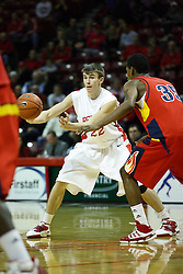 11 December 2010: Jon Ekey passes off when approached by Brad Birton during an NCAA basketball game between the Illinois - Chicago Flames (UIC) and the Illinois State Redbirds (ISU) at Redbird Arena in Normal Illinois.