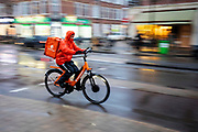 In Utrecht rijdt een bezorger van Thuisbezorgd.nl door de stromende regen.<br /> <br /> In Utrecht cyclists ride in the pouring rain.