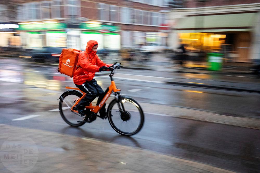 In Utrecht rijdt een bezorger van Thuisbezorgd.nl door de stromende regen.<br /> <br /> In Utrecht cyclists ride in the pouring rain.