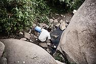 Zimbabwe, mand henter vand ved natural spring.