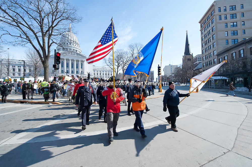 "A group of firefighters marches outside of the state Capitol to protest proposed budget cuts on March 1, 2011 in Madison, Wisconsin. A judge ordered Tuesday that the state Capitol should be opened to the public ""during business hours and at times when governmental matters, such as hearings, listening sessions and court arguments are being conducted."" Although protesters, occupying the Capitol for 15 days, were not forced to leave, the public was barred from entering the building since it closed at 4 p.m. on Sunday. (Photo by Brian Kersey)"