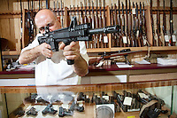 Mature merchant aiming with rifle in gun shop