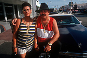 A portrait of an exiled Cuban couple sitting on the hood, or bonnet of their car in Miami Beach, on 15th May 1996, in Miami, Florida USA. (Photo by Richard Baker / In Pictures via Getty Images)