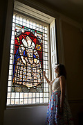 Long Melford, Suffolk. National Trust Volunteers at Long Melford Hall. Pictured is Beth Turner looking at one of the stained glass windows. <br /> <br /> Picture: MARK BULLIMORE