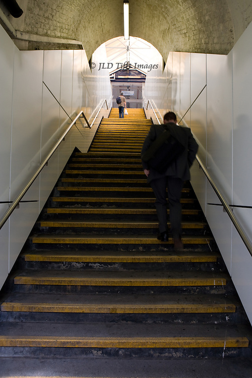 Stairway to the platform at Earlsfield Station, 2007, after remodelling.  The magical mystical quality of the older version has vanished.  Back view of a woman near the top and a man in the middle ground climbing the stair.