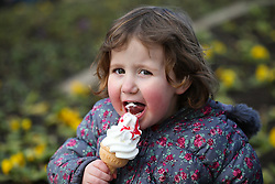 © Licensed to London News Pictures. 18/02/2016. Leeds, UK. 3-year-old Enola enjoys an ice-cream despite the cold weather at Roundhay Park in Leeds, West Yorkshire. Forecasters are predicting temperatures to drop below zero this week as snow and ice are set to batter Britain. Photo credit : Ian Hinchliffe/LNP