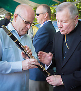 Archbishop Aymond blesses Pete Fountain's clarinet before Tim Laughlin uses it to perform at French Quarter Festival - Friday