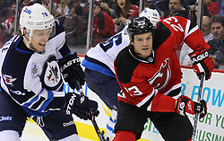 Jan 17; Newark, NJ, USA; New Jersey Devils right wing David Clarkson (23) and Winnipeg Jets center Bryan Little (18) race for the loose puck during the second period at the Prudential Center.