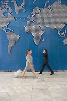 Business woman with suitcase passing businessman using mobile phone near world map
