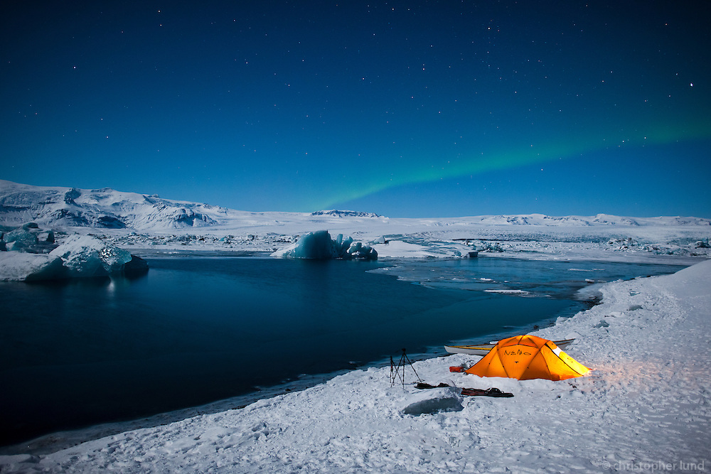 Winter camping at Breiðármerkurlón Glacier Lagoon in Southeast Iceland. Northern Lights (Aurora Borealis) dancing above in the moonlit sky.