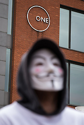 "© Licensed to London News Pictures . 23/05/2015 . Manchester , UK . A man wearing an "" Anonymous "" mask at a demonstration , organised by "" The People's Assembly "" , against austerity in Piccadilly Gardens in Central Manchester , attended by approximately 2000 people . Photo credit : Joel Goodman/LNP"