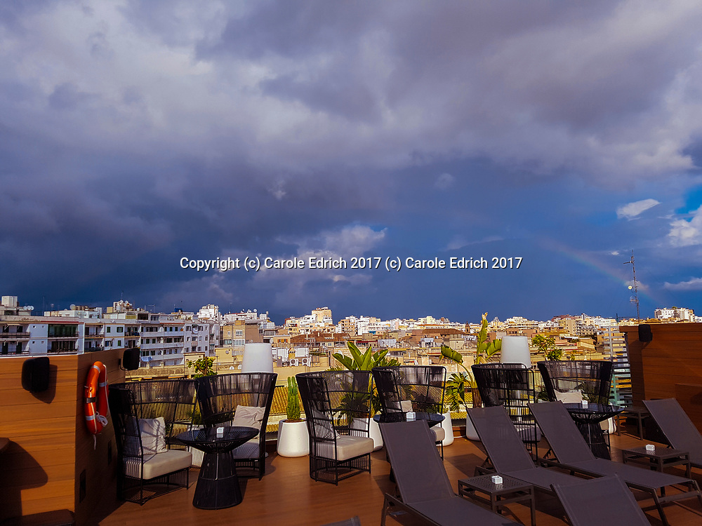 Rainbow in distance over Nakar Hotel roof, showing Nakar hotel rooftop decor. (c) Carole Edrich 2017