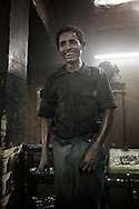 Egypt, Cairo:A recycling worker stands inside a factory in  Moqattam, the christian coptic quarter in Cairo where live 40.000 Zabbaleen (garbage collectors). ph.Christian Minelli.