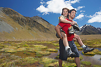 Man giving woman piggy-back ride through pond near mountains