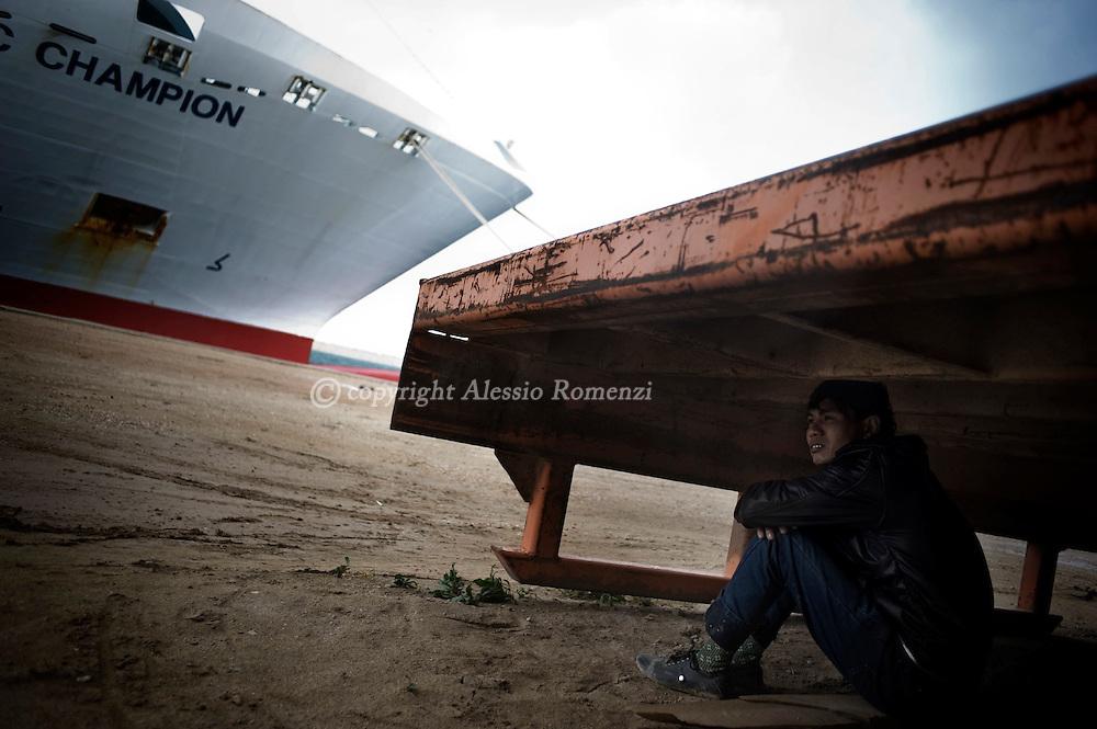 Libya, Benghazi. A Bangladeshi worker waiting on the port of Benghazi some boat that will permit them to leave Libya, on February 26, 2011. ALESSIO ROMENZI