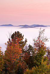 Morning fog and fall foliage as seen from the fire tower at Milan Hill State Park in Milan, New Hampshire.