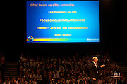 Employees listen to an executive at their corporate rally day, held for 3,000 UK staff at Excel