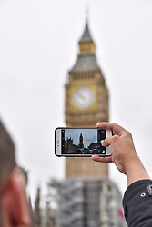 © Licensed to London News Pictures. 21/08/2017. London, UK. London, UK.  21 August 2017.  A tourist takes a photo.  Big Ben, the bell inside the clock tower known as The Elizabeth Tower, will be silenced ahead of four years of restoration work to the glass on the clock face, the hands of the clock and the tower itself.  One clock face will continue to show the correct time throughout the renovations, driven by a temporary electric motor.  It is planned that the clock will be restarted for Big Ben to chime at New Year, on Remembrance Sunday and other special occasions.  Photo credit : Stephen Chung/LNP