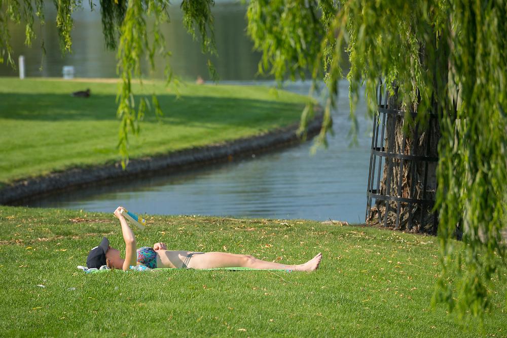 Canada, British Columbia,Okanagan Valley, Kelowna, girl reading on lawn