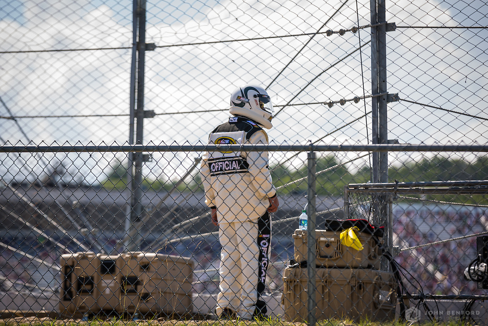 A race official watches the NH 301 NASCAR Sprint Cup race from outside the fence at the New Hampshire Motor Speedway.