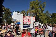 "Dominga Sierra (holding sign) protests, along with about 1,000 demonstrators who participated in Occupy Tucson at Military Plaza in Armory Park, Tucson, Arizona, USA.  The Occupy Tucson organizers created the movement in solidarity with the Occupy Wall Street movement in New York and the Occupy Together movement across the USA.  Sierra said, ""I think that I am thinking of the children and their future because everything is so hard.  There will be no jobs.  I have 18 grandchildren and I worry about every one of them.  I think that it is time to get together and fight for our rights.  I always thought what is wrong with people.  They don't get out and fight for their rights.  I think that being out of work did it.""..The leaders of this movement are the everyday people participating in a movement with many de-centralized goals, with an over-arching theme of protesting government corruption from corporate money and national income disparity. We use a tool called the ""General Assembly"" to facilitate open, participatory and horizontal organizing between members of the public. We welcome people from all colors, genders and beliefs to participate in our movement. .."