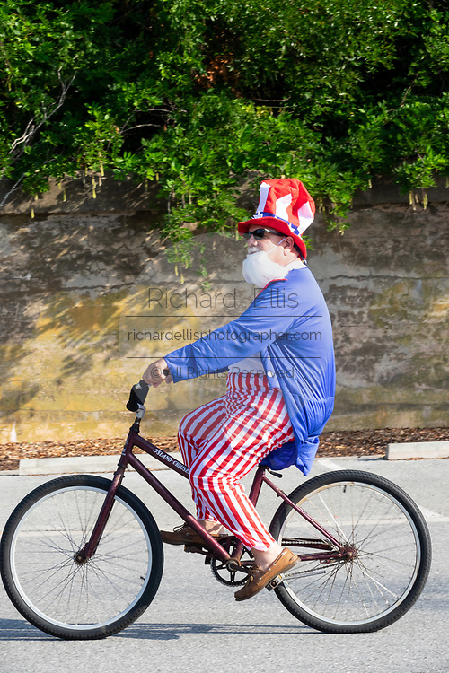 A man dressed in an Uncle Sam costume rides his bicycle in the annual Independence Day golf cart and bicycle parade July 4, 2019 in Sullivan's Island, South Carolina. The tiny affluent Sea Island beach community across from Charleston holds an outsized golf cart parade featuring more than 75 decorated carts.