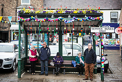 © Licensed to London News Pictures. 27/04/2016. Thirsk UK. Picture shows the bus stop in Thirsk that has been Yarn Bombed. Under the cover of Darkness 300 Yarn bombing street artist's have covered the Town centre of Thirsk, the group has covered bollards, flower pots, the bus stop, tree's, benches, even the local police station. The knitted creations took over 750 balls of wool & have been placed along the route of the Tour De Yorkshire which will pass through the town during it's final stage from Middlesborough to Scarborough on Sunday.  Photo credit: Andrew McCaren/LNP