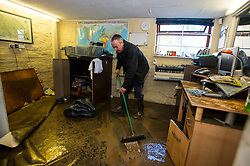 © Licensed to London News Pictures. 29/12/2015. York, UK. PETER HALE sweeps mud from the office floor at hi mechanics business on on Huntingdon Road in central York following heavy flooding. Further rainfall is expected over coming days as Storm Frank approaches the east coast of the country. Photo credit: Ben Cawthra/LNP