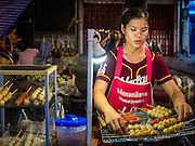 30 JUNE 2016 - BANGKOK, THAILAND:  A grilled meat vendor at her cart in the Pak Khlong Talat sidewalk market. Sidewalk vendors around Pak Khlong Talat, Bangkok's famous flower market, face eviction if they reopen on July 1. As a part of the military government sponsored initiative to clean up Bangkok, city officials have been trying to shut down the sidewalk vendors around the flower market. The vendors were supposed to be gone by the end of March, but city officials relented at the last minute with a compromise allowing vendors to stay until June 30. When vendors dismantled their booths after business on June 30, they weren't sure if they will be allowed to reopen July 1. Some vendors have moved to new locations approved by the government but many have not because they can't afford the higher rents in the new locations.    PHOTO BY JACK KURTZ