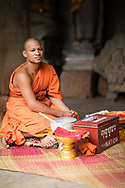 Monk giving blessings with donation boc, Angkor Wat, Siem Reap, Cambodia