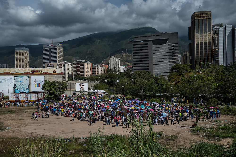 CARACAS, VENEZUELA - JANUARY 15, 2015: Hundreds of people wait in line to enter a state-run Bicentenario supermarket in Caracas. Despite being a petro-state with one of the largest oil reserves in the world, basic food goods such as cooking oil, milk, chicken, coffee, rice, sugar and corn meal are difficult to find in stores across Venezuela. PHOTO: Meridith Kohut