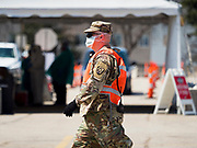 "26 APRIL 2020 - DES MOINES, IOWA: A soldier with the Iowa Army National Guard walks past the COVID-19 drive through testing site in Des Moines. Iowa started mass testing Saturday, with a drive through testing site in a parking lot in downtown Des Moines. The testing this weekend is considered a ""soft opening"" for the program and tests were reserved for medical professionals and first responders. Despite numerous outbreaks in meat packing plants throughout Iowa, members of the public have not been able to get tested. On Saturday, 25 April, there were 5,092 confirmed cases of COVID-19 (Coronavirus / SARS-CoV-2) in Iowa (an increase of 647 since Friday, April 24) and 112 deaths in Iowa caused by COVID-19.         PHOTO BY JACK KURTZ"