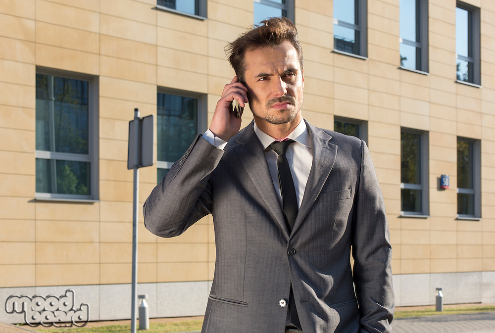 Businessman using cell phone against office building