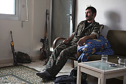 © Licensed to London News Pictures. 28/09/2014. Al-Yarubiyah, Syria. A Syrian-Kurdish YPG fighter watches television in the Syrian town of Al-Yarubiyah.<br /> <br /> Facing each other across the Iraq-Syria border, the towns of Al-Yarubiyah, Syria, and Rabia, Iraq, were taken by Islamic State insurgents in August 2014. Since then The town of Al-Yarubiyah and parts of Rabia have been re-taken by fighters from the Syrian Kurdish YPG. At present the situation in the towns is static, but with large exchanges of sniper and heavy machine gun fire as well as mortars and rocket propelled grenades, recently occasional close quarter fighting has taken place as either side tests the defences of the other. Photo credit: Matt Cetti-Roberts/LNP