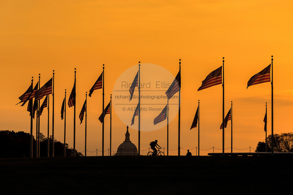 Flags fluttering around the Washington Monument silhouetted by sunset in Washington, DC.