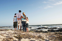 Family standing together on beach back view